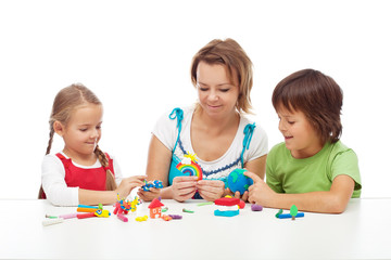Woman and kids playing with colorful clay
