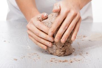 hands knead rye dough