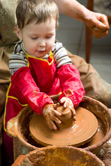 boy potter at work in the studio. two years old