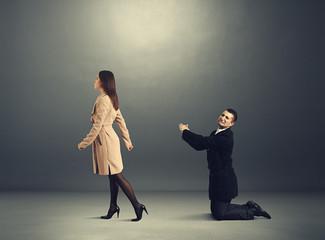sad man bending before woman