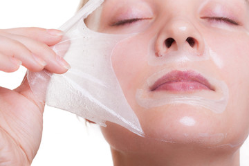 Portrait blond girl in facial mask. Beauty and skin care.