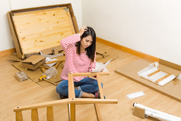 Asian woman assembling new chair with instruction