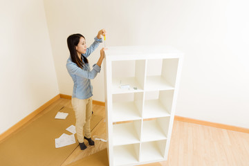 Asian woman assemble a white bookshelf