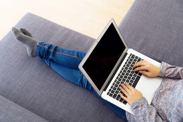 Asian woman using laptop on sofa