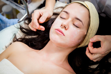 Cosmetologist doing facial mask to face of woman