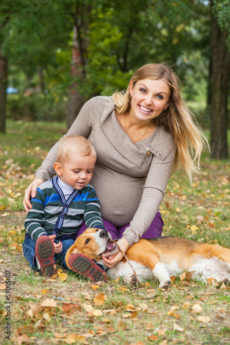 Family walk with pet in autumn park