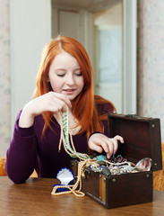 Teen girl looks jewelry in treasure chest