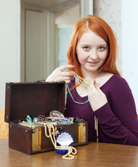 red-headed  girl tries necklace in home
