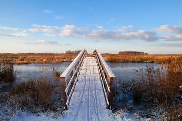 wooden bridge through river in snow