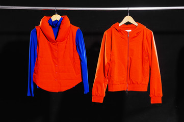 Red jacket hanging on hanger-black background