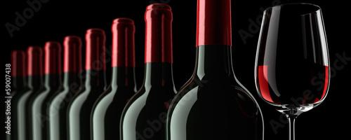 Weinflaschenreihe mit Glas