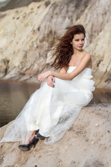 bride sitting in a baren land
