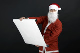 Santa Claus reading gift list, isolated on black background