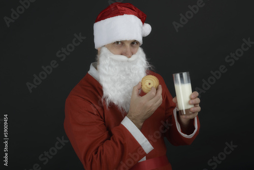 Portrait of Santa Claus Drinking milk from glass and  cookies