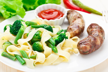 Fettuccine with vegetables and fried sausages