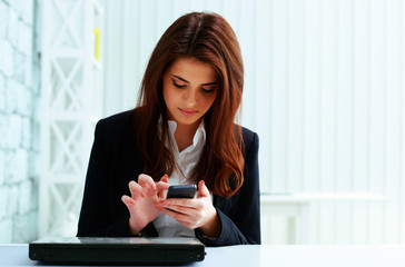 Young serious businesswoman typing on her smartphone in office