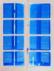 Fenêtre blanche, volets bleus fermés