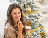 Woman eating candy with latte macchiato near christmas tree