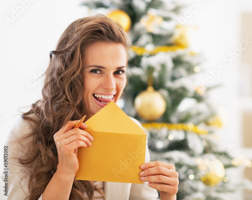 Happy young woman licking envelope in front of christmas tree