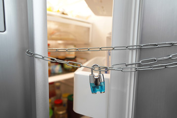 Dieting concept. Refrigerator, chain and lock