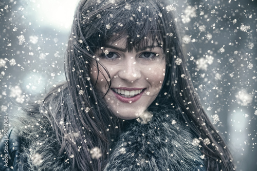 Smiling young woman in a winter snow day