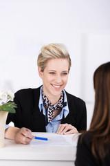 lächelnde mitarbeiterin im kundengespräch
