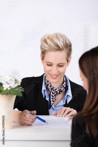 mitarbeiterin am empfang erklärt ein formular