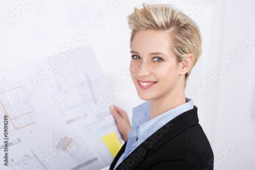 lächelnde blonde frau mit bauplan