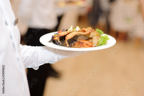 waiter holding plate with grilled fish