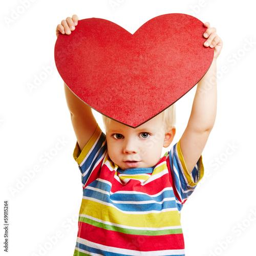 Kind zeigt rotes Herz als Symbol für Liebe