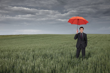 Man with orange umbrella in field