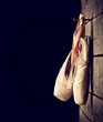 Used ballet shoes hanging on wooden background