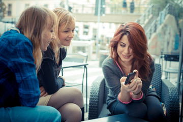 three friends woman at the bar using phone