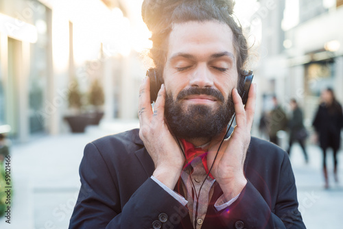 Stylish elegant dreadlocks businessman listening to music