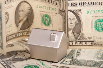 Many dollar banknotes, house model; concept of buying a house