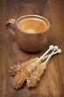 cup of coffee and caramel sugar on sticks, selective focus