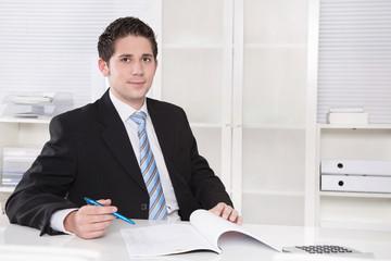 Jungunternehmer - Portrait Mann jung in Anzug im Büro sitzend