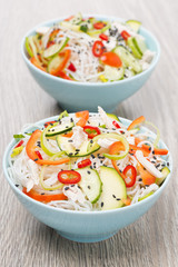 two bowls of salad with vegetables, rice noodles and chicken