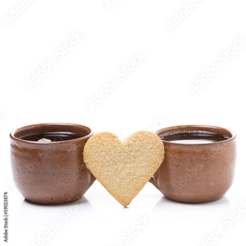two cups of coffee and cookie in the shape of hearts
