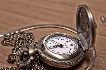 Pocket watch chain on the background of a wooden Desk