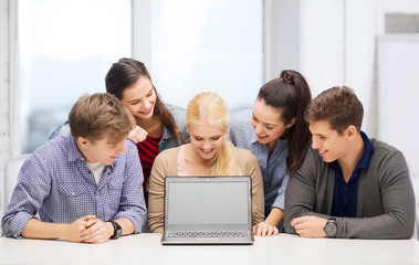 smiling students looking at blank lapotop screen