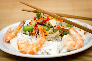 Shrimps and rice on the plate with vegetables