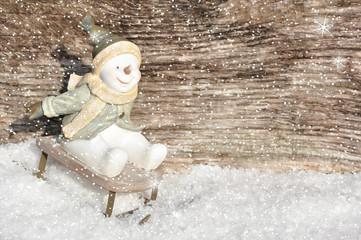 Schneemann rodelt mit Holzhinergrund