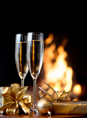 Two champagne glasses in front of fireplace