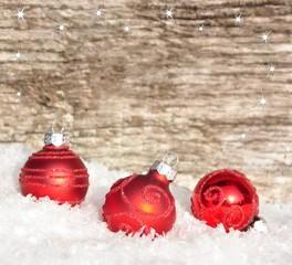 Drei Weihnachtskugeln-Schnee- Holzhintergrund
