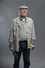 Gardener senior man smiling with hat holding scoop. Studio shot