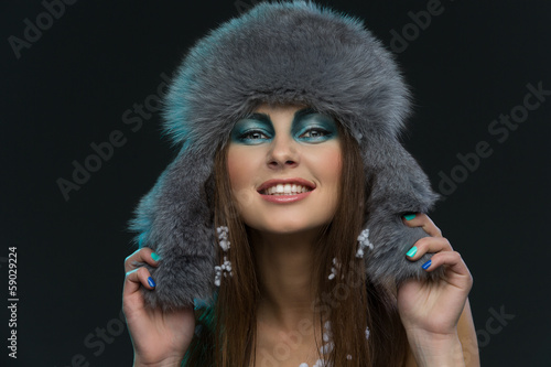 Girl in fur hat with snow