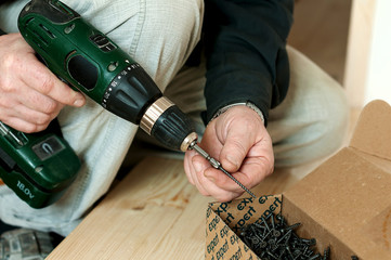 Man installs nail into the screw gun