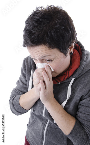woman with the flu blowing nose into tissue