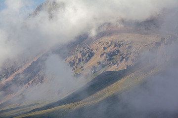 Clouds coverig rocks in mountains of Tien Shan